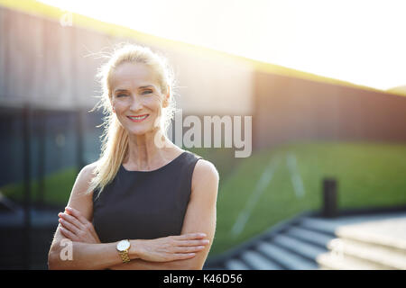 Close up portrait of happy businesswoman standing outside with her arms crossed. - Stock Photo