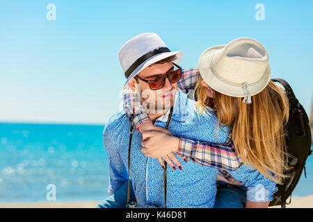 Happy man carrying his girlfriend on a piggyback ride both smiling and looking very happy enjoying their vacation - Stock Photo