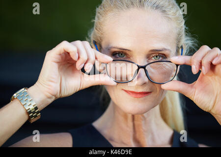 Close up portrait of glad businesswoman holding spectacles. - Stock Photo