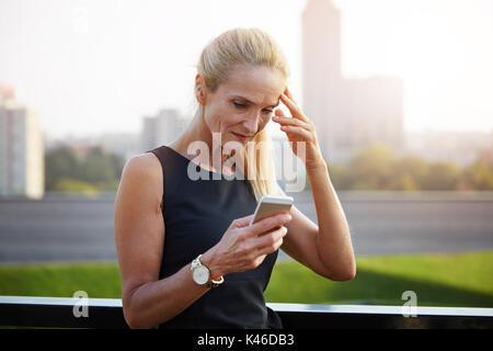 Close up portrait of upset businesswoman reading text message.
