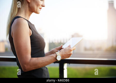 Portrait of mature businesswoman looking for information online on tablet. - Stock Photo