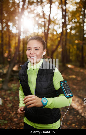 Happy sportswoman jogging through the forest and listening music. - Stock Photo