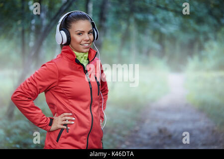 Portrait of confident happy sportswoman holding hands on hips and smiling. - Stock Photo