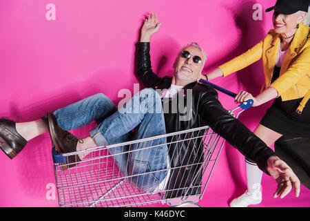 Smiling stylish senior woman pushing shopping trolley with joyful senior man having fun - Stock Photo