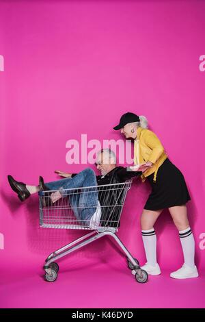 Side view of smiling stylish senior woman pushing shopping trolley with joyful senior man having fun - Stock Photo