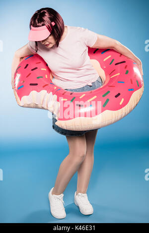 stylish woman standing with swimming tube in form of doughnut - Stock Photo