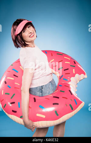 smiling stylish woman with swimming tube in form of doughnut looking at camera - Stock Photo