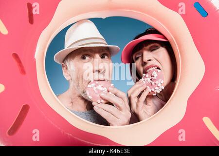 portrait of elderly couple eating sweet doughnuts into swimming tube - Stock Photo