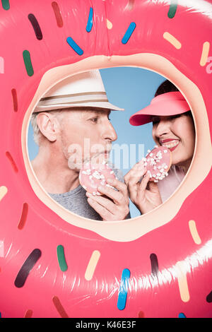 portrait of elderly couple eating sweet doughnuts into swimming tube - Stock Photo