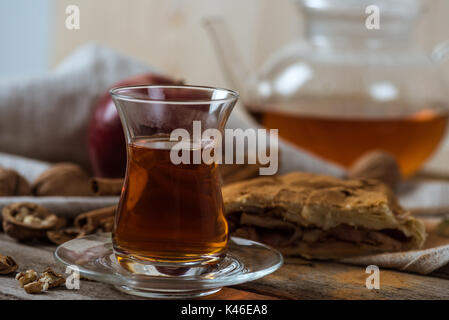 hot tea in glass cup and homemade apple pie with walnuts on rustic wooden tabletop - Stock Photo