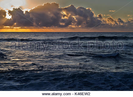 The sun rising over the Pacific Ocean, taken from Boulder Beach, NSW, Australia. - Stock Photo
