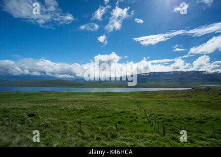 Iceland - Fjord and mountains with snow behind wide green fields - Stock Photo