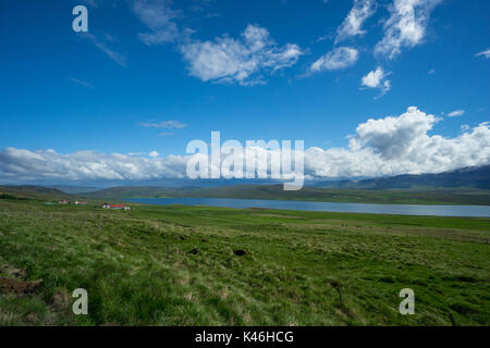 Iceland - Blue lake betwen green fields and mountains - Stock Photo