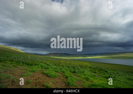 Iceland - Dramatic sky with dark clouds and thunderstorm coming over lake - Stock Photo