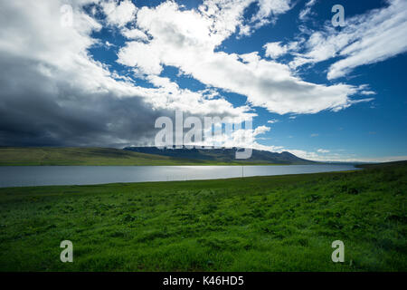 Iceland - Dark thunderstorm coming over blue fjord between green landscape - Stock Photo