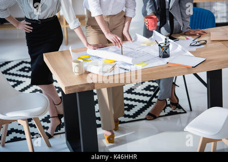 cropped shot of architects in formal wear working with blueprints at table - Stock Photo
