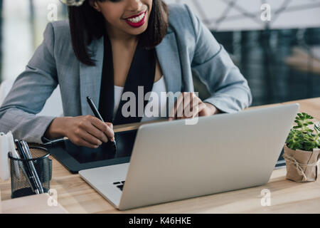 Cropped shot of smiling woman looking at laptop while using graphic tablet