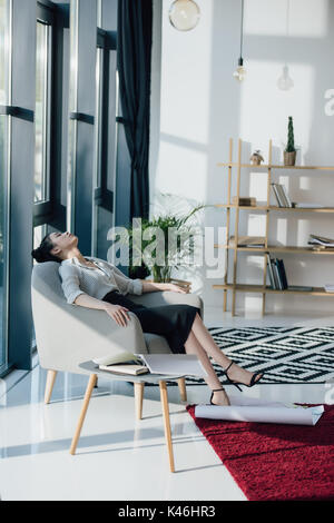 Young tired asian businesswoman sitting in chair with closed eyes - Stock Photo