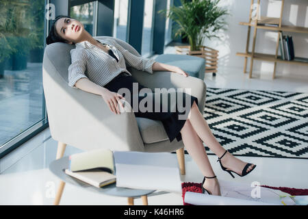Young tired asian businesswoman sitting in chair and looking at window  - Stock Photo
