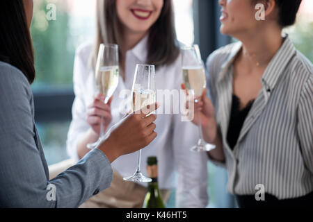 cropped shot of businesswomen in formal wear drinking champagne indoors - Stock Photo