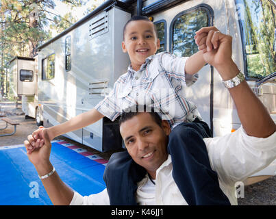 Happy Hispanic Father and Son In Front of Their Beautiful RV At The Campground. - Stock Photo