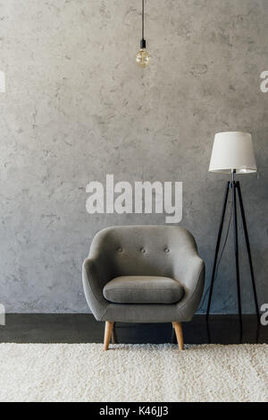 Cozy grey armchair on white carpet and modern lamp in empty room - Stock Photo