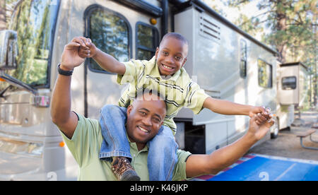 Happy African American Father and Son In Front of Their Beautiful RV At The Campground. - Stock Photo