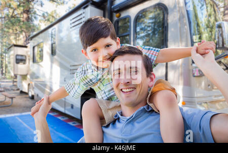 Happy Young Caucasian Father and Son In Front of Their Beautiful RV At The Campground. - Stock Photo