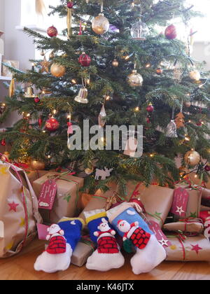 Knitted stockings and wrapped presents under a christmas tree - Stock Photo