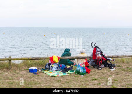 Young muslim women sitting having a picnic with a young child at East Beach, Shoeburyness, Essex, UK. - Stock Photo