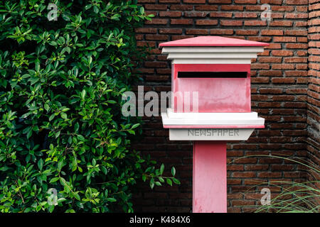 Outbox outside the house with bushes and orange brick walls. - Stock Photo