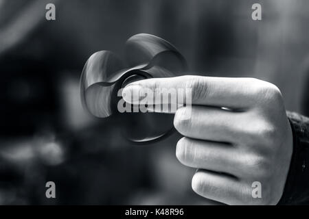 A hand playing with fidget spinner in the park. - Stock Photo