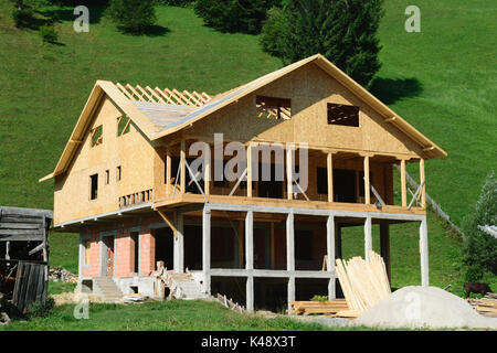 house under construction and green hills in the background - Stock Photo
