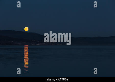 Full moon rising over some hills on a lake, perfectly reflecting on water - Stock Photo