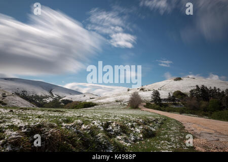 Long exposure photo of a mountain scenery with green grass and melting snow near a road, under a blue sky with moving - Stock Photo