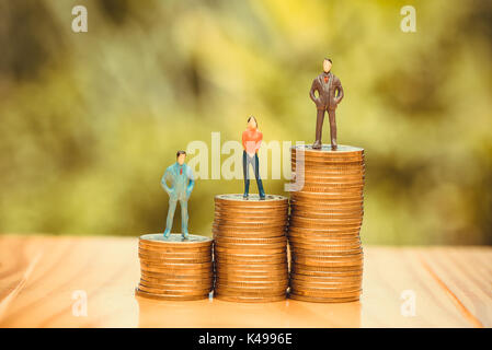 Miniature people, small figures businessmen and woman on top of coins. Money and Financial, Business Growth concept. - Stock Photo
