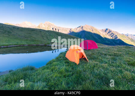 Silhouettes of hikers are reflected in the lake with Mont De La Saxe on the background Courmayeur Aosta Valley Italy - Stock Photo