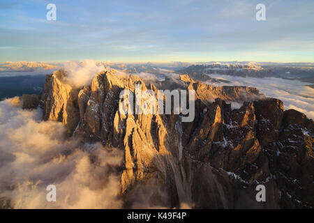 Aerial view of the mountain range of Odle surrounded by clouds. Dolomites Val Funes Trentino Alto Adige South Tyrol - Stock Photo