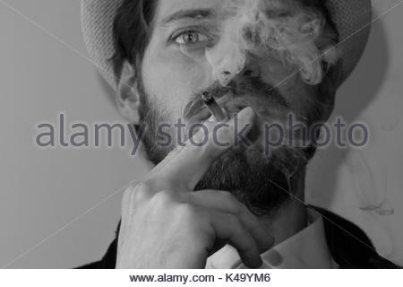 portrait of a young man smoking. Model release available - Stock Photo