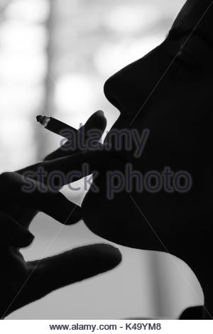 Silhouetted profile of a young man smoking. Model release available - Stock Photo