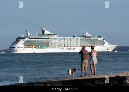 Holidaymakers watching from Calshot Spit on Southampton Water southern England UK with a backdrop of the cruise - Stock Photo