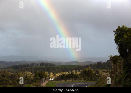 Rainbow close-up  looking towards the flank of Kakepuku Volcano from Te Awamutu, North Island, New Zealand - Stock Photo