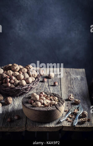 Delicious walnuts and hazelnuts with on rustic wooden table - Stock Photo