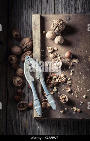 Delicious walnuts and hazelnuts with with old nutcracker - Stock Photo