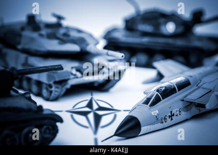 Toy Tanks, Military Jet And Nato Emblem - Stock Photo