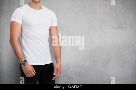 Man wearing blank t-shirt isolated on gray background with copy space - Stock Photo
