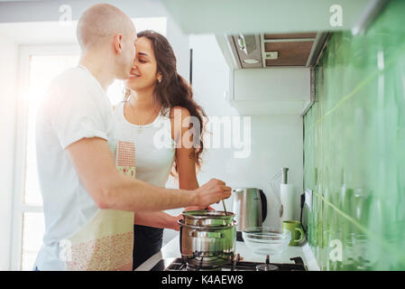Happy young couple preparing on the stove - Stock Photo