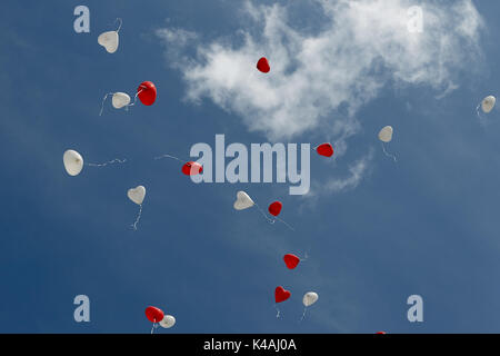 At a wedding, balloons in the shape of a heart rise into the sky - Stock Photo