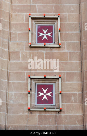 Maltese cross on a church. The cross symbol associated with the Order of St. John since 1567 - Stock Photo