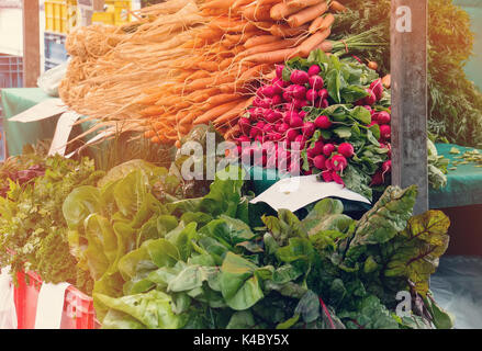 Fresh vegetables - carrots, radishes, lettuce, sell at a farmers market in autumn Sunny day with other vegetables. - Stock Photo
